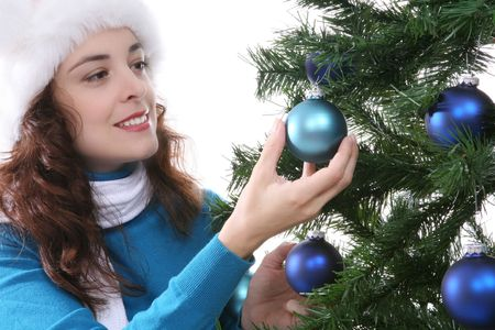 A beautiful woman hanging Christmas ornaments on the tree photo