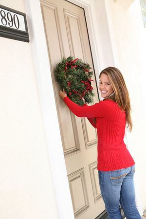 A beautiful woman hanging a Christmas wreath on her home photo
