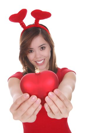 A pretty young woman holding a heart shaped Valentines ornament Imagens