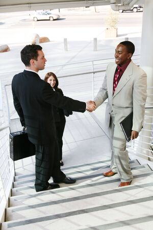 Two handsome business men shaking hands to confirm a deal