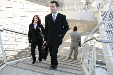 Attractive man and woman business people walking up the stairs