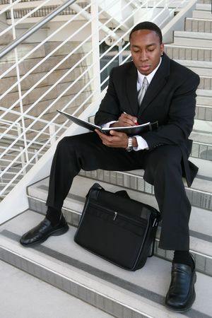 coporate: An attractive business man reading and taking notes on the stairs