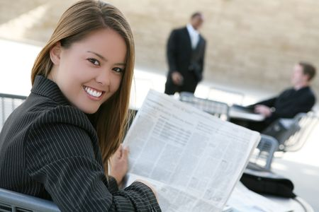 A successful, pretty business woman reading the newspaper photo