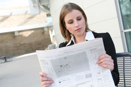 stockbroker: A pretty  business woman reading the newspaper outside her company
