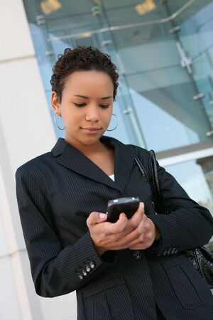 An african american business woman answering cell phone Stock Photo - 2667814