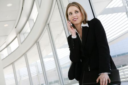 A pretty business woman on the phone at her company photo