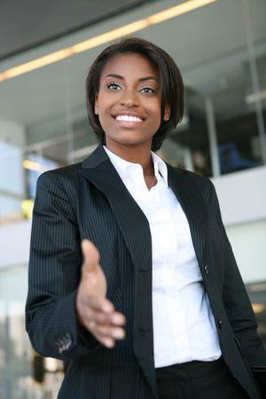 saluta: Una donna americana africana graziosa di affari che offre una stretta di mano