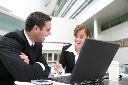 An attractive man and woman business team working on computer photo