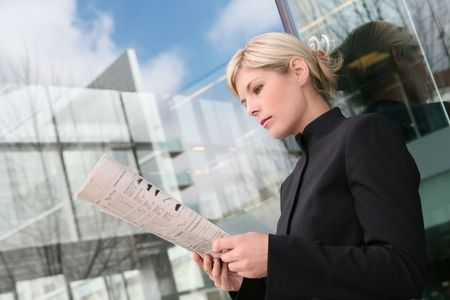 A beautiful blonde business woman reading newspaper photo
