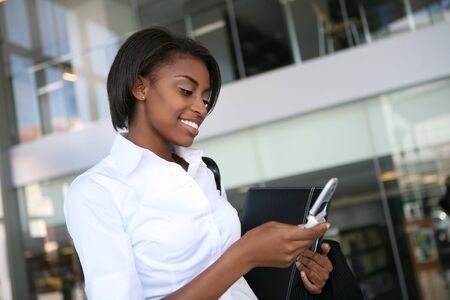 Pretty african american business woman checking her cell phone Stock Photo - 2730333