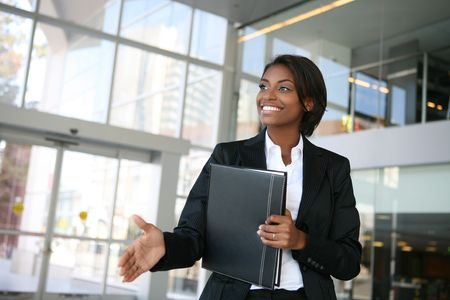 business interview: A pretty african american business woman offering a handshake