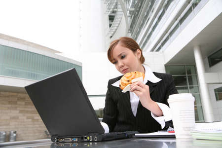 A pretty young woman eating and working on computer