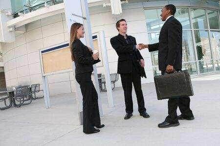 A business team (men and woman) shaking hands in agreement photo