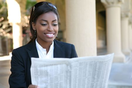 smart investing: A pretty african american business woman reading newspaper