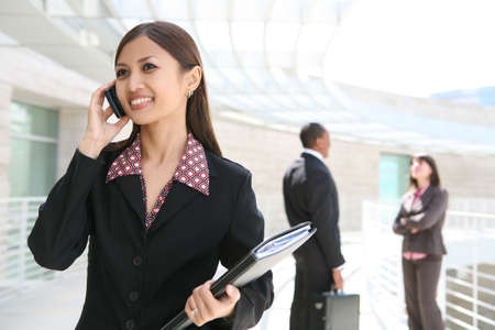 A pretty asian business woman on cell phone with co-workers in background Stock Photo - 2851472
