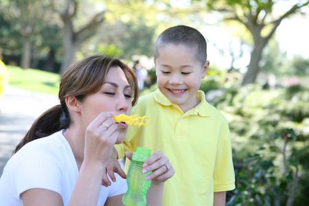 An attractive mother and son blowing bubbles in the park photo