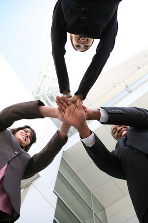 A diverse business team with hands together at company photo