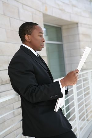 A handsome business man reading the newspaper at company photo