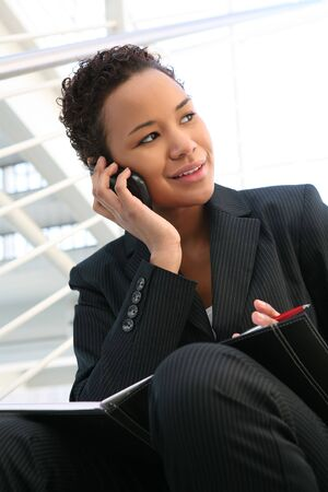 A pretty african american business woman at her company on the phone photo