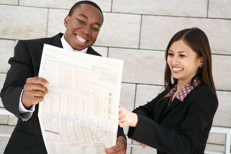 financial newspaper: An attractive diverse business team readin the financial newspaper