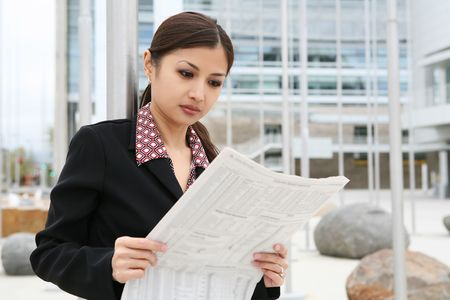 A pretty asian business woman reading the newspaper outside company Imagens