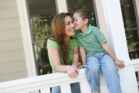 A young boy kissing his pretty mother on the cheek Stock Photo - 2935013