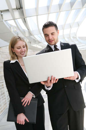 An attractive man and woman business team with computer at company photo