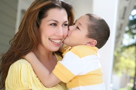 smooch: A young boy kissing his pretty mother on the cheek