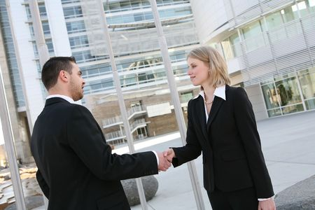 A handsome business team shaking hands outside office building Фото со стока