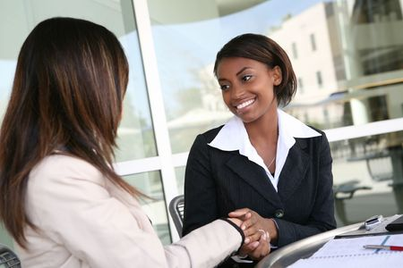 greet: A pretty african american business woman shaking hands