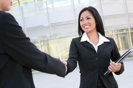 courtier: Une belle jeune femme d'affaires asiatiques se serrant la main  Banque d'images