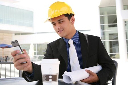 A handsome business construction man looking at cell phone photo