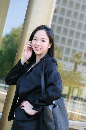 phone business: A beautiful asian business woman at golden office building