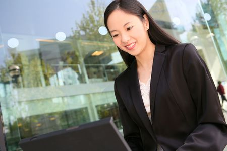 A pretty asian business woman working on the laptop photo