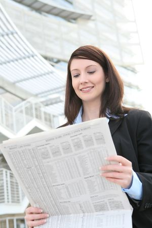 A pretty business woman reading the newspaper outside company photo