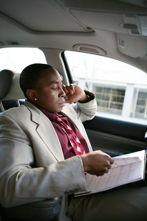 A handsome african american business man in car doing work