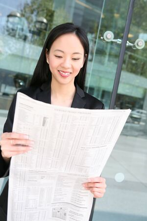 Pretty asian business woman reading the newspaper outside office building photo