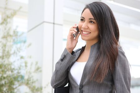 A pretty young woman on the phone at her office building Stock Photo - 3099533