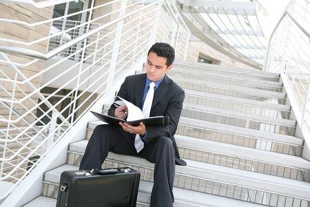 reviewing: A handsome hispanic business man on the stairs reviewing his notes