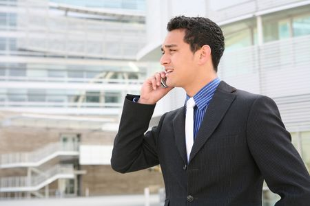 phone support: A handsome hispanic business man on the phone in front of office building Stock Photo