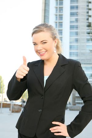 A pretty blonde business woman with her thumbs up outside office building Stock Photo - 3110522