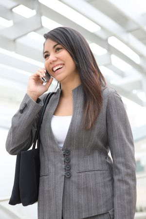 A pretty young woman on the phone at her office building photo