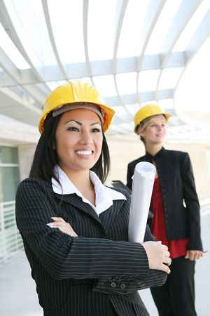 site: Two pretty women working as  architects on a construction site Stock Photo