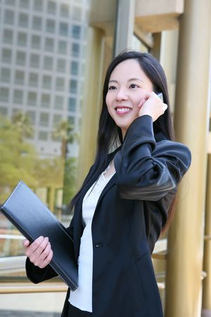 A beautiful asian business woman at golden office building on the phone photo
