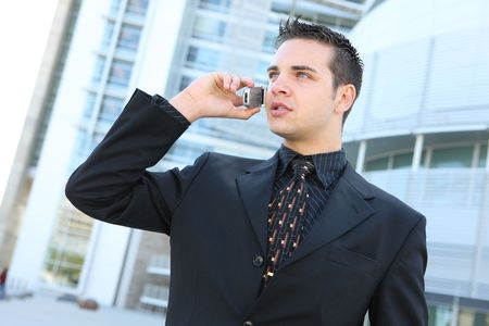 A young, handsome business man talking on the phone at office building Stock Photo - 3146078
