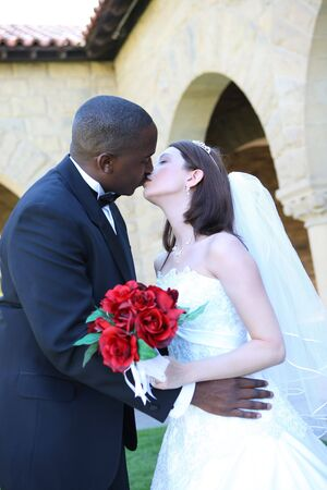 An attractive man and woman wedding couple kissing outside church photo