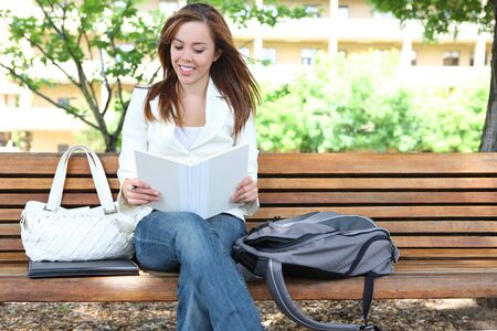 A cute young woman reading on a bench at college photo