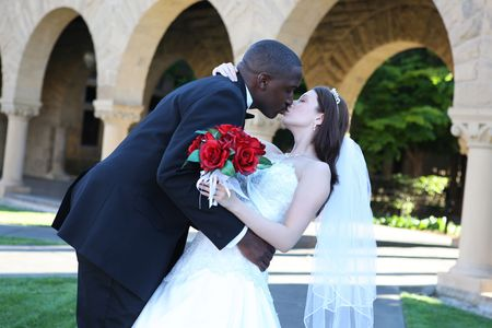 An attractive man and woman wedding couple kissing outside church