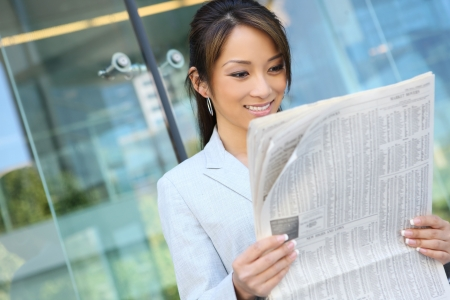 사무실 건물에서 신문을 읽는 예쁜 아시아 비즈니스 여자