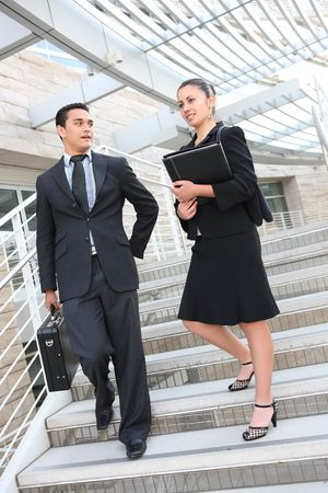 Attractive man and woman business team on stairs at office building Stock Photo